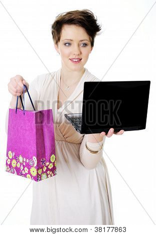 Young woman with shopping bag and laptop