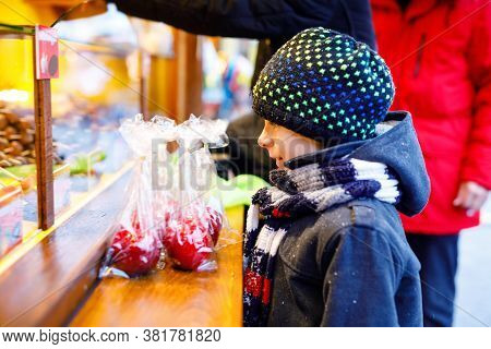 Little Cute Kid Boy Near Sweet Stand With Sugared Apples And Chocolate Fruits. Happy Child On Christ