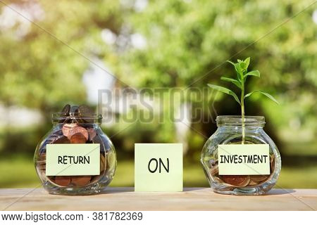 Return On Investment. Plants Growing From Coins Outside The Glass Jars On Blurred Green Natural Back