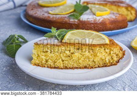 Cutting Up And Piece Of Freshly Baked Lemon Pie, Tart Or Semolina Cake On Plate Served Lemon Wedges