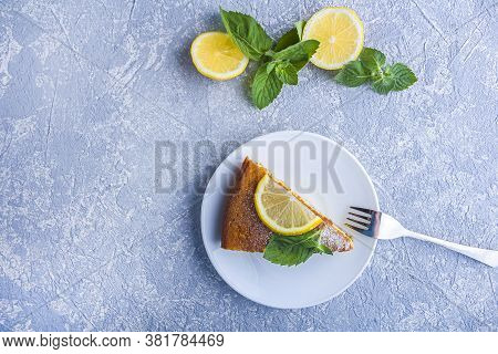 Piece Of Freshly Baked Lemon Pie, Tart Or Semolina Cake On Plate Served Lemon Wedges And Mint. Homem