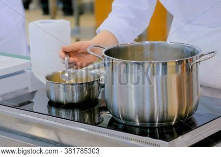 Chef Hand Stirring Rice And Millet With Spoon In Steel Pot On Electric Stove At Cuisine Of Restauran