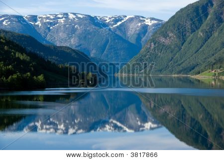 A view across the Hardanger fjord from Ulvik. The early morning sun is creating beautiful reflections in the tranquil water. poster