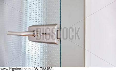 Open glass door in the office with doorknob and key in the door lock as a header