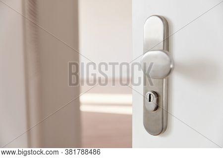 Open front door or apartment door with a view of an empty hallway