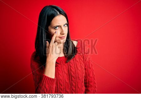 Young brunette woman with blue eyes wearing casual sweater over isolated red background Pointing to the eye watching you gesture, suspicious expression