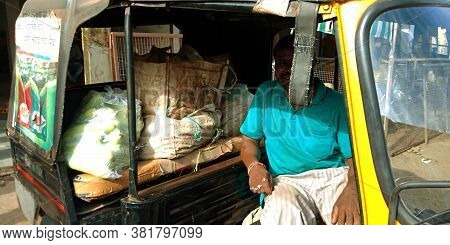 District Katni, India - August 07, 2019: Asian Man Seating On Auto Loaded With Bunches Of Vegetable