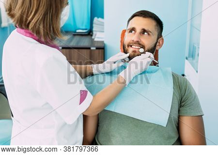 A Man Treats His Teeth At The Dentist. Dental Examination At The Dentist. Sound Teeth. A Snow-white