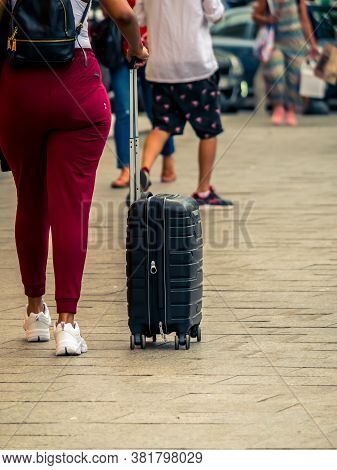 Woman With A Travel Suitcase Or Luggage Going Or Coming From The Airport.
