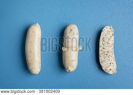 White Sausages Presentation With Peeled Skin And Wurst Section Isolated On A Blue Table. Top View Of