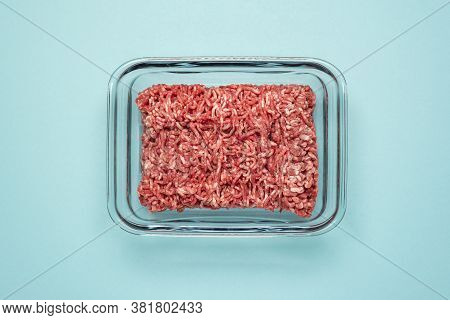 Above View With Ground Beef In A Glass Food Container On A Blue Colored Table. Ground Beef In A Glas
