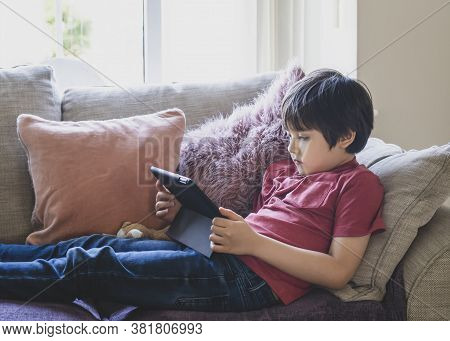 Mixed Race Kid Sitting On Sofa Watching Cartoons On Tablet,portrait 6-7 Year Old Boy Playing Game On