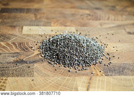 Chia Seeds Are Sprinkled On A Wooden Plank. Close-up Chia Seeds On A Wooden Surface With Copy Space.