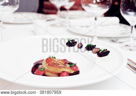 Foie gras with port sauce on table in an expensive French restaurant, toned