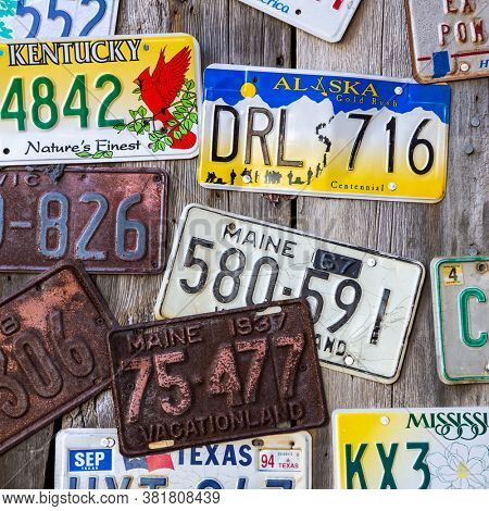 Bar Harbor, Maine, USA - August 28 2014: Old car license plates on a wall in Bar Harbor. In the United States, each jurisdiction has a unique design, usually displaying a symbol of the issuing state.