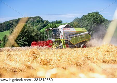 Bavaria / Germany - August 20, 2020: Claas Tucano 420 Combine Harvester Threshes Grain In An Agricul