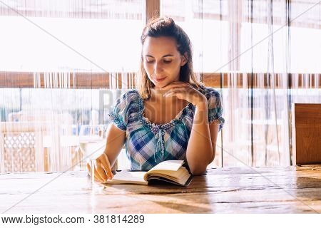 Woman reading book at wine bar in vacation. Woman relaxing in wine bar in vacation. Vacation lifestyle. Beautiful woman portrait. Lifestyle. Concept of vacation lifestyle. Happy people in vacation. Healthy people. Young people in vacation.Vacation. Espres