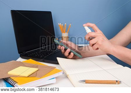 Woman Wiping Smartphone Screen With Disinfectant Spray Or Sanitizer Sitting On Modern Workspace. Dis
