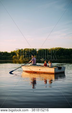 Young Family Go By Boat On The River Or Lake In Summertime. Photography For Ad Or Blog About Family