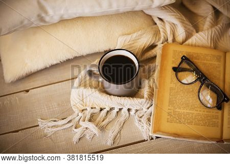 From Above Metal Mug Of Hot Drink And Eyeglasses On Old Opened Textbook Beside Warm Blanket And Soft