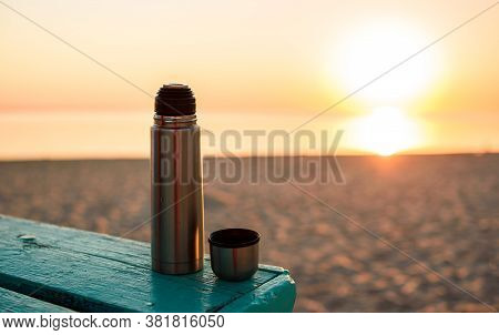 Thermos With Fragrant Hot Tea On A Blue Bench, On The Shore By The Sea. Sandy Deserted Beach.