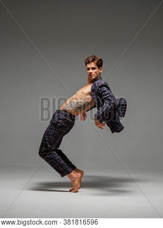Stylish Young Guy Breakdancer Dancing In Suit Barefoot Isolated On Gray Background. Dance School Pos