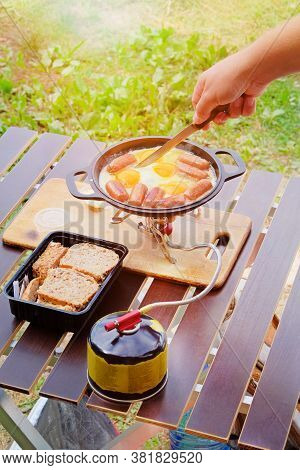 Camping Food Making. Fried Eggs And Sausages On Pan On Tourist Gas Burner. Camper Preparing Food In