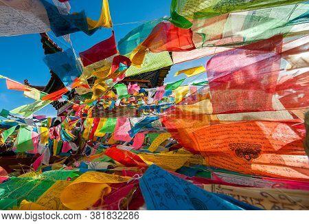 Dêqên, China - 08 17 2009: Colorful Tibetan Buddhist Prayer Flags Hanging From A Pagoda Near Kawa Ga