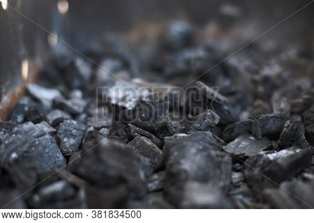 Coals Lie With A Container Of A Charcoal Grill. The Coals In The Grill Are Extinct.