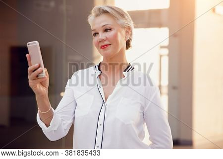 Beautiful stylish middle aged woman with gray hair uses smartphone