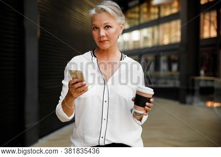 Gorgeous middle aged businesswoman with cup of coffee posing against the black wall.