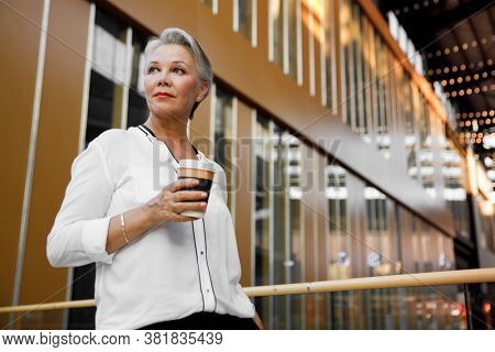 Gorgeous middle aged businesswoman with cup of coffee posing in the interior of the business center.
