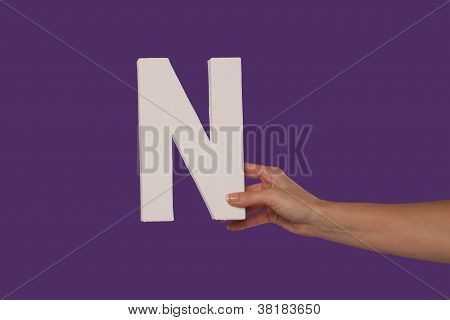 Female Hand Holding Up The Letter N From The Right
