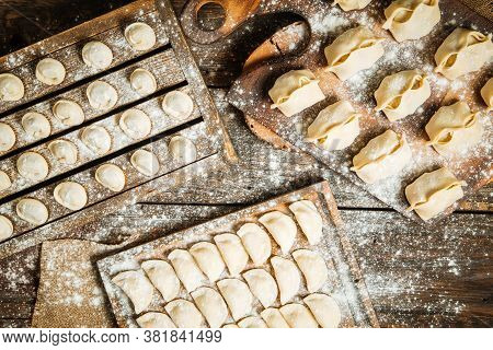 Top View On Variety Of Semi-finished Dumplings On The Wooden Boards With Flour