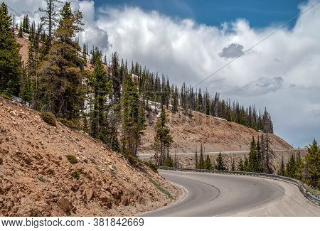 High In The Mountains In Colorado, The Highway Curves And Winds And Travelers View The Mountains Whi