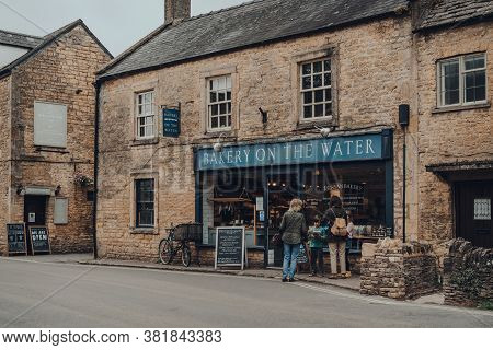 Bourton-on-the-water, Uk - July 12 2020: People Looking At Products On A Window Display Of Bakery On