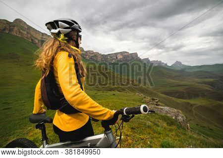 A Slender Girl Cyclist With Red Hair In A Helmet And With A Backpack Stands On A Mountain Bike High