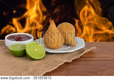 Coxinha. Traditional Fried Brazilian Food With Chicken. Background With Defocused Fire