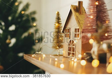 Merry Christmas. Stylish Christmas Wooden House, Glitter Christmas Tree And Golden Reindeer In Festi