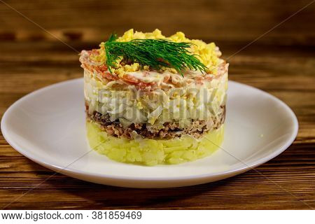 Traditional Russian Salad Mimosa On Wooden Table. Layered Salad With Sardine, Onion, Potatoes, Carro