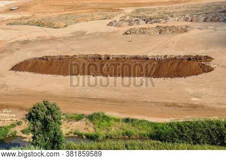 A Large Pit Dug In The Field. Large Pit. Deep Sand Pit Dug For Trash In The Field. House Constructio
