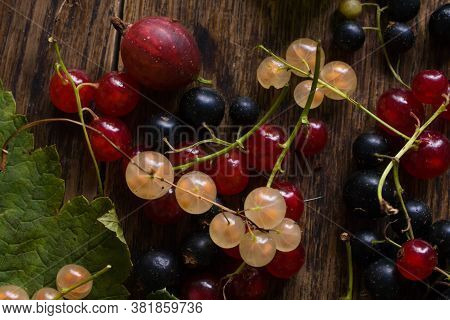 Flat Lay. Red Currant, Blackcurrant, White Currant With Leafs On The Old Wooden Table