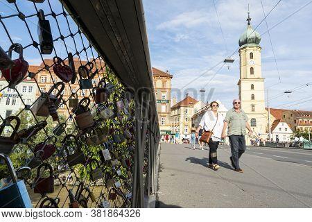 Graz, Austria. August 2020.  A Couple Walking On The Erzherzog Johann Bridge Where Lovers Declare Th