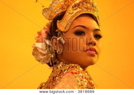 Cultural Dancer In Malaysia Against Yellow Background In Traditional Costume And Head Dress.