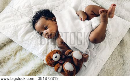 Portrait Of Cute Adorable Little African American Baby Looking At Camara In A White Bedroom