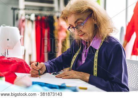 Portrait Of Elderly Woman Fashion Designer Stylish Sitting And Working With Sewing Machine.attractiv