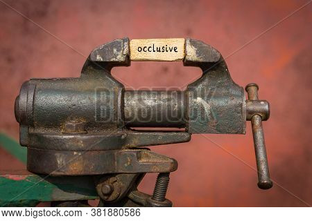 Concept Of Dealing With Problem. Vice Grip Tool Squeezing A Plank With The Word Occlusive
