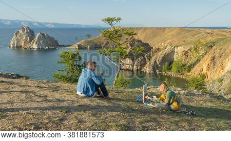Russia, Irkutsk Region, Village Of Khuzhir, August 2020: Girl Draws A Picture On The Shore Of A Lake
