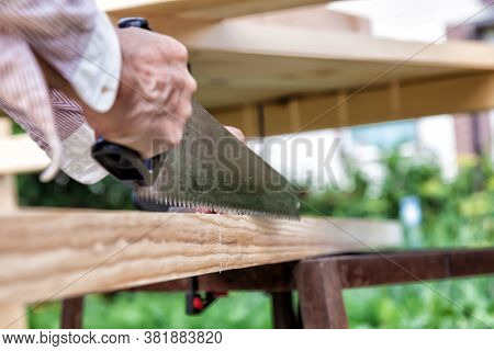 A Hand-held Metal Saw With A Black Plastic Handle With Sharp Teeth In The Hands Of A Carpenter When