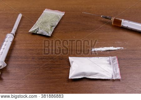 Different Type Of Drugs: Cocaine, Heroin Syringe And Dried Cannabis On A Table. Drug Use, Crime And
